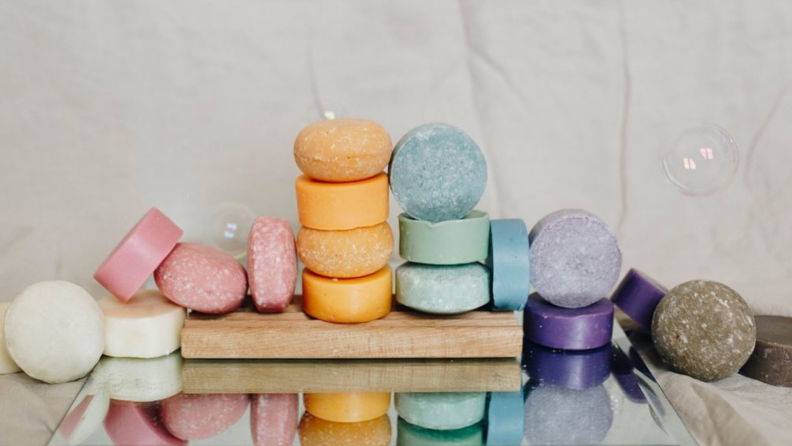 Shampoo bars in white, pink, orange, blue, purple, and gray stacked on top of each other in a line going across a table.
