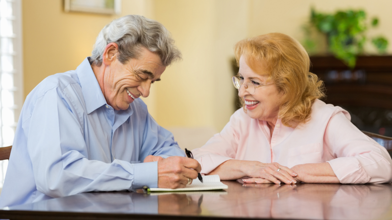 A senior couple finishing paperwork at home.