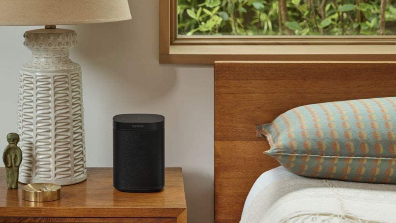 A Sonos speaker sits on a nightstand in a bedroom.