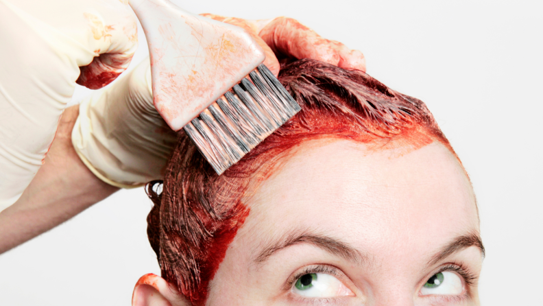 A woman getting her hair dyed red