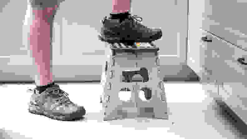 A person wearing sneakers steps on a low plastic stool