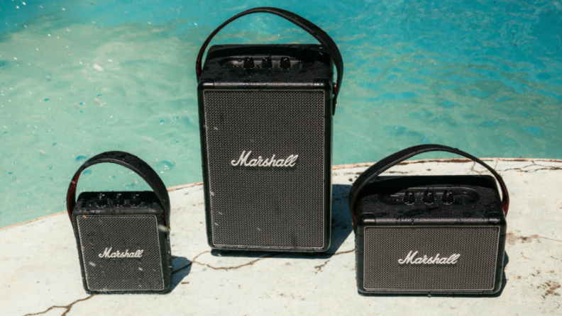Three Marshall loudspeakers next to a swimming pool.
