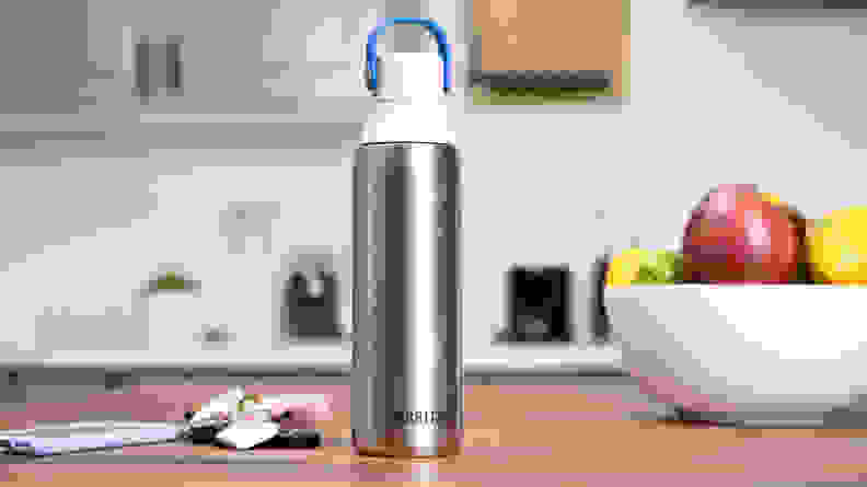 Silver water bottle sitting on countertop in kitchen.