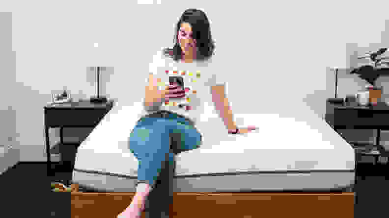 a person sits on the end of the Purple mattress on their phone
