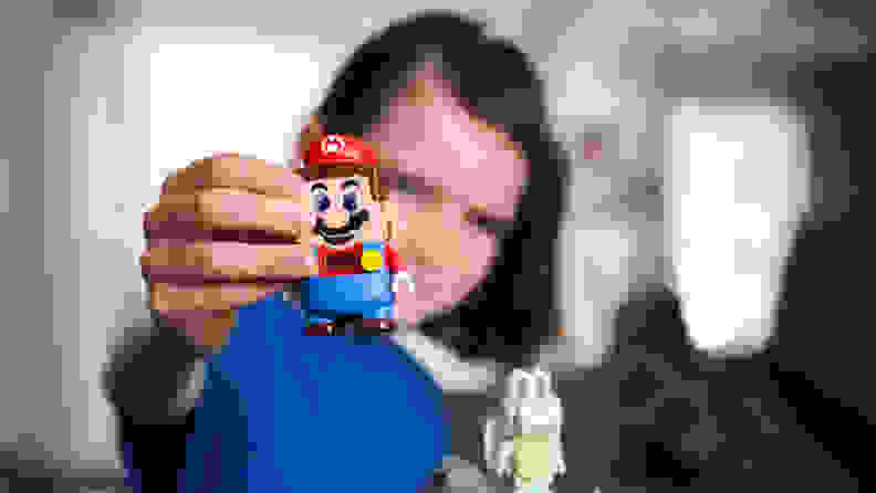 A child holds the Super Mario Lego toy.