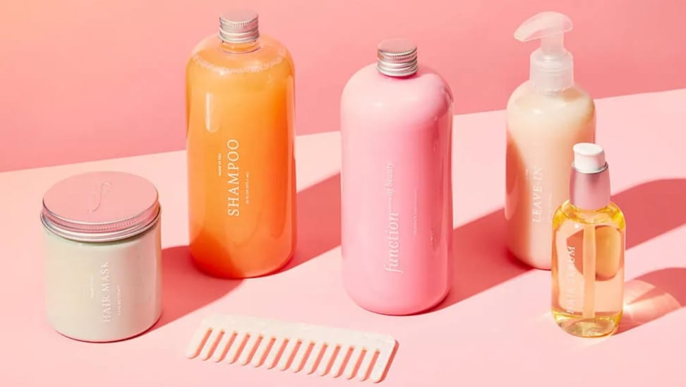 Multi-colored hair products and comb in front of pink background.