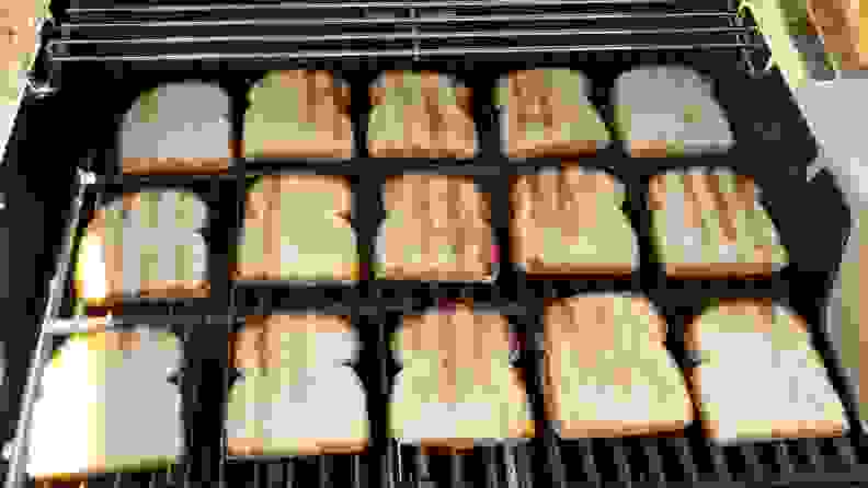 Grilled slices of white bread neatly arranged across the grate of a Weber grill.