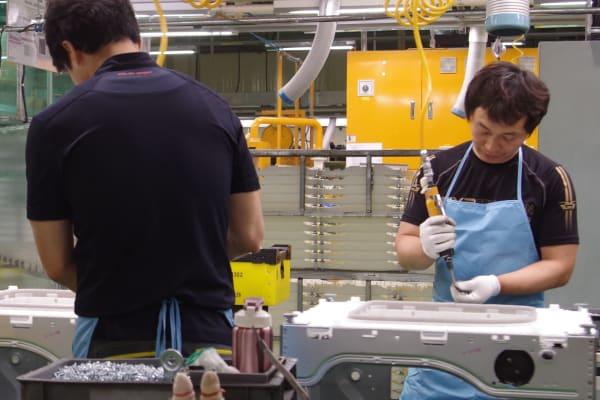 Workers assemble LG washing machines.