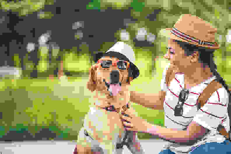 Woman sits with dog wearing hat
