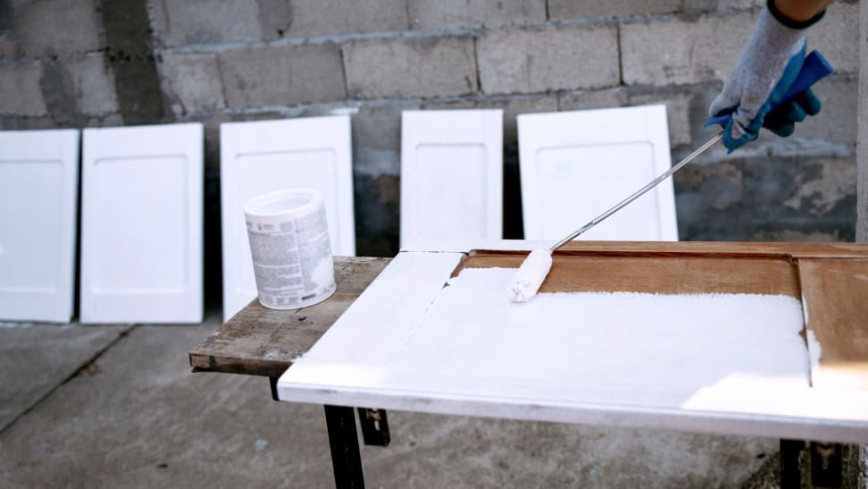 Gloved hand using paint roller to paint cabinets white outdoors.