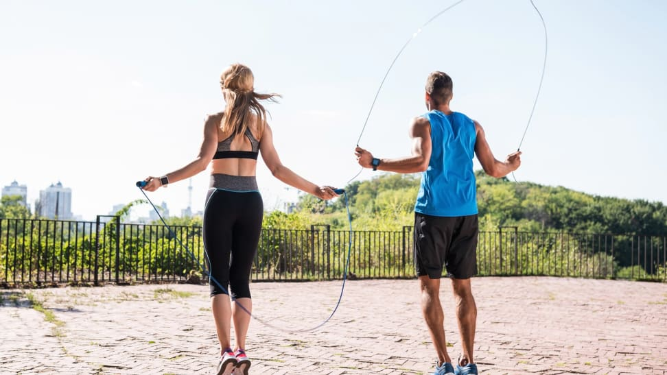 Man and woman jumping rope outside and overlooking city.