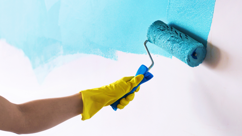 Hand wearing yellow rubber glove using paint roller to paint wall blue.