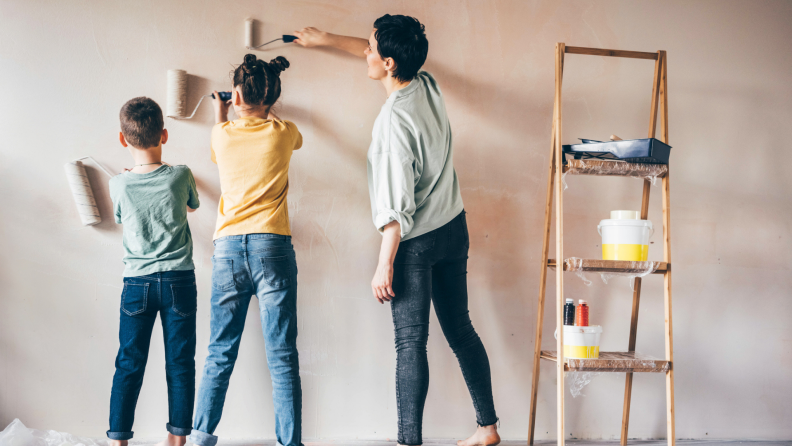 Family of three painting walls with interior paint next to a wooden ladder