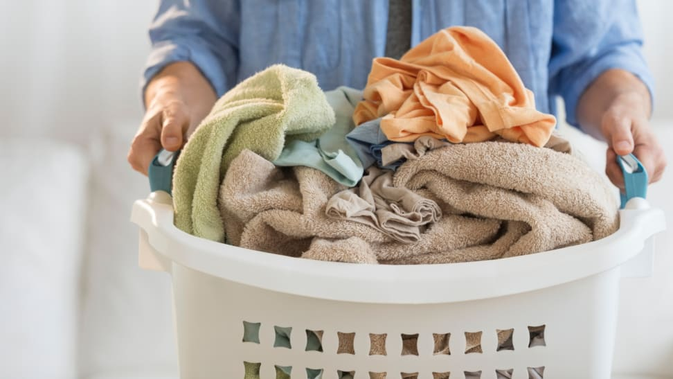 Man holding laundry basket filled with clothes.