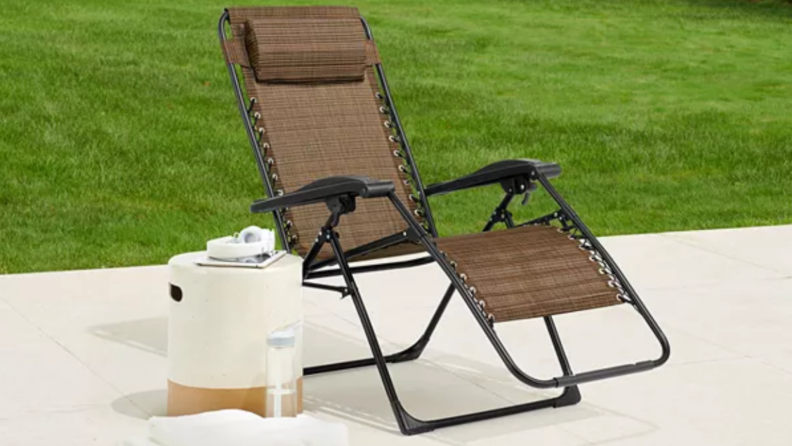 Product shot of tan Sonoma Goods For Life antigravity chair outdoors on patio next to cooler.