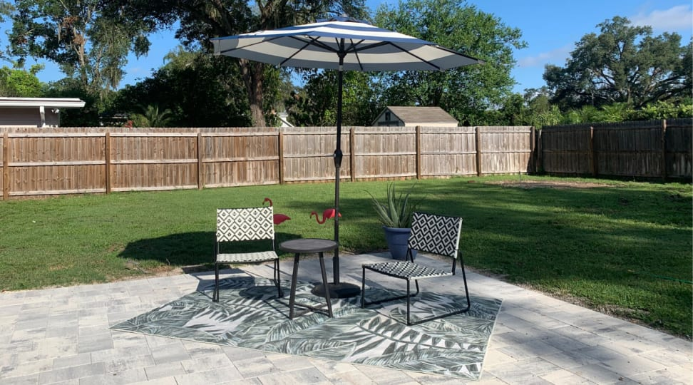 A patio set up with an outdoor Ruggable, two chairs, small table, and an umbrella.