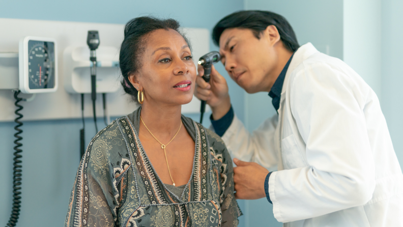 A doctor examines a patient's ears.