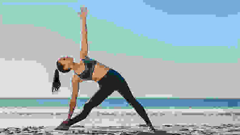 A woman doing yoga on the beach.