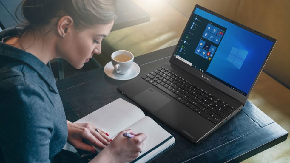A woman works in a cafe with a dynabook satellite and a book.