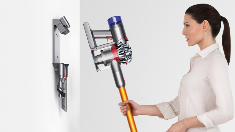 An image of a woman hanging her cordless vacuum from a wall hanger.